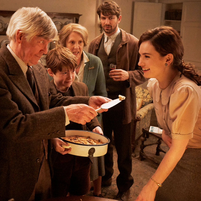 A still from the movie The Guernsey Literary & Potato Peel Pie Society, showing the characters eating a potato peel pie.