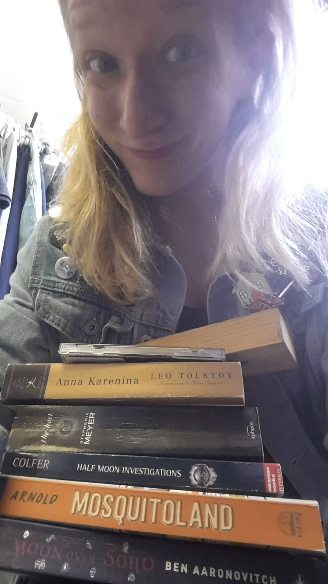 A girl grins while clutching a stack of books. This is a selfie.