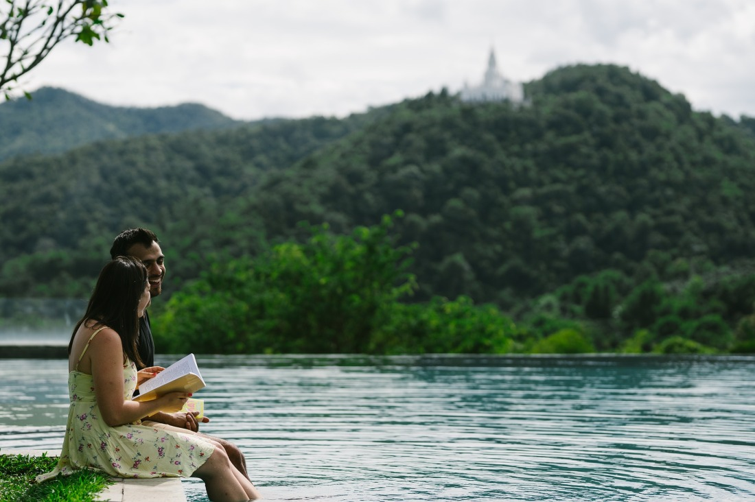Boy and girl reading book next to mountains, forest and river