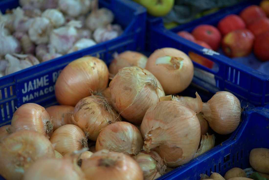 Crate of onions on sale at a farmers' market, with garlic, apples and other produce in the background