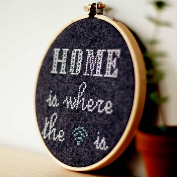 "A photograph of an embroidery hoop holding black cloth onto which is embroidered the phrase, ""Home is where the WiFi is""."