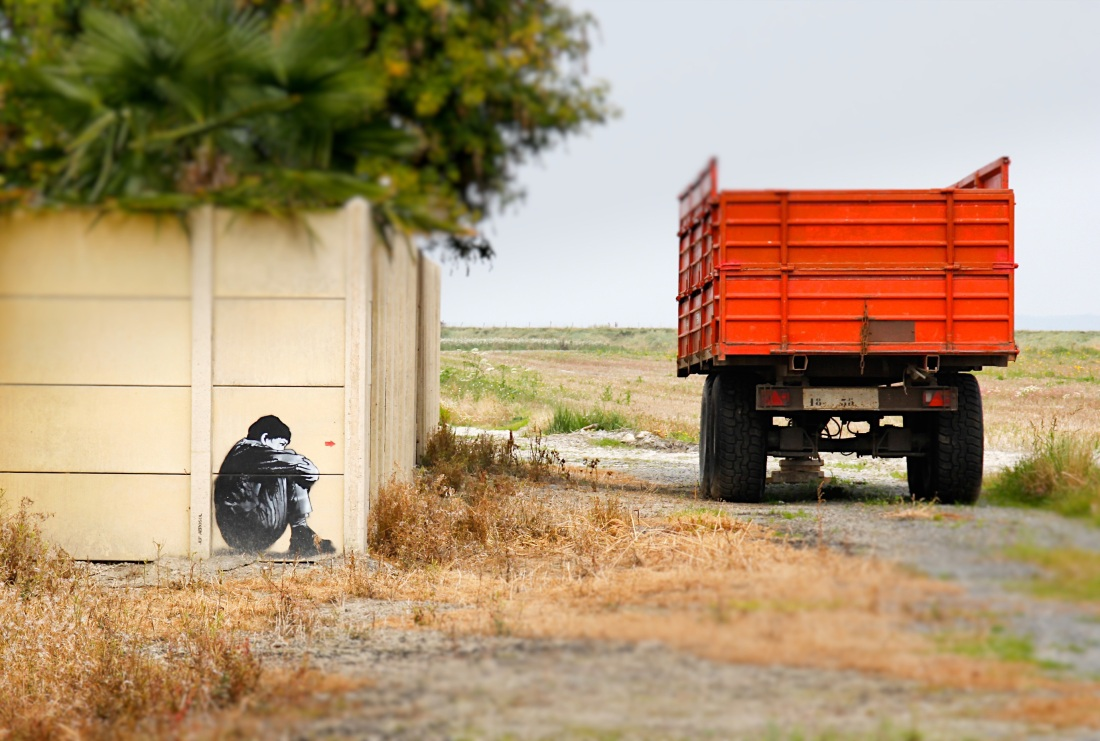 A red truck, to the right of the frame, drives down a dirt road. It passes a white wall on which graffiti depicting a small huddled boy is pictured. Green bushes are seen over the wall.