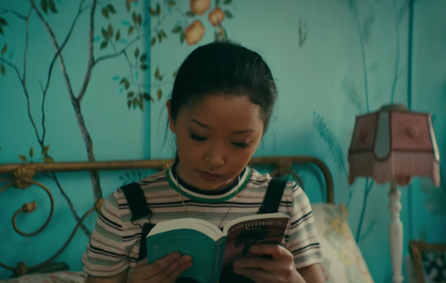 A still from the movie To All The Boys I've Loved Before, showing Lara Jean reading a book.