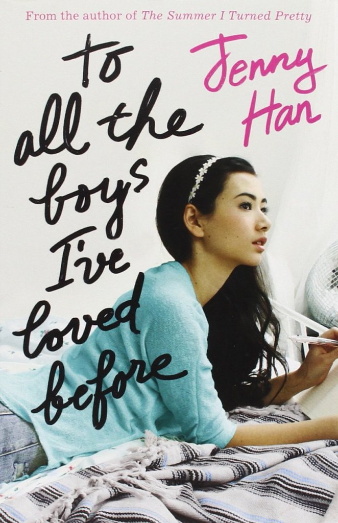 "The original book cover of To All The Boys I've Loved Before by Jenny Han. The image shows the words ""to all the boys I've loved before"" and ""Jenny Han"" in handwritten script, with a photograph of a teenage girl with long dark hair, wearing an alice band, a blue sweater and denim shorts, lying on her bed, holding a pen over a paper and gazing off into the distance against a white background."