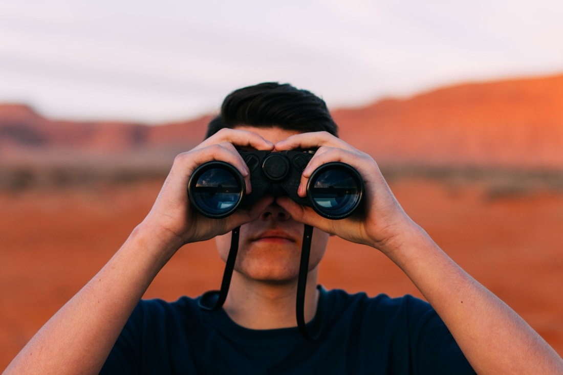 man looking through binoculars in desert