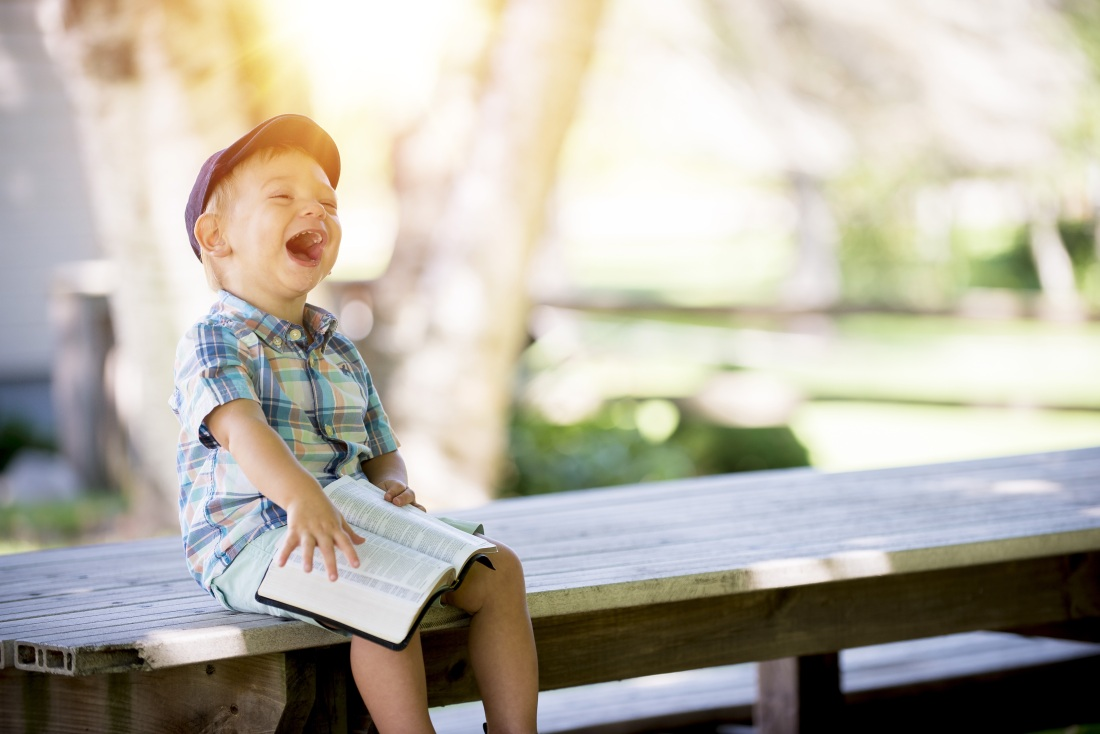young boy laughs while holding book and sitting on bench