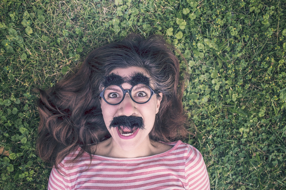 girl with dark hair lying on grass with funny face mask on
