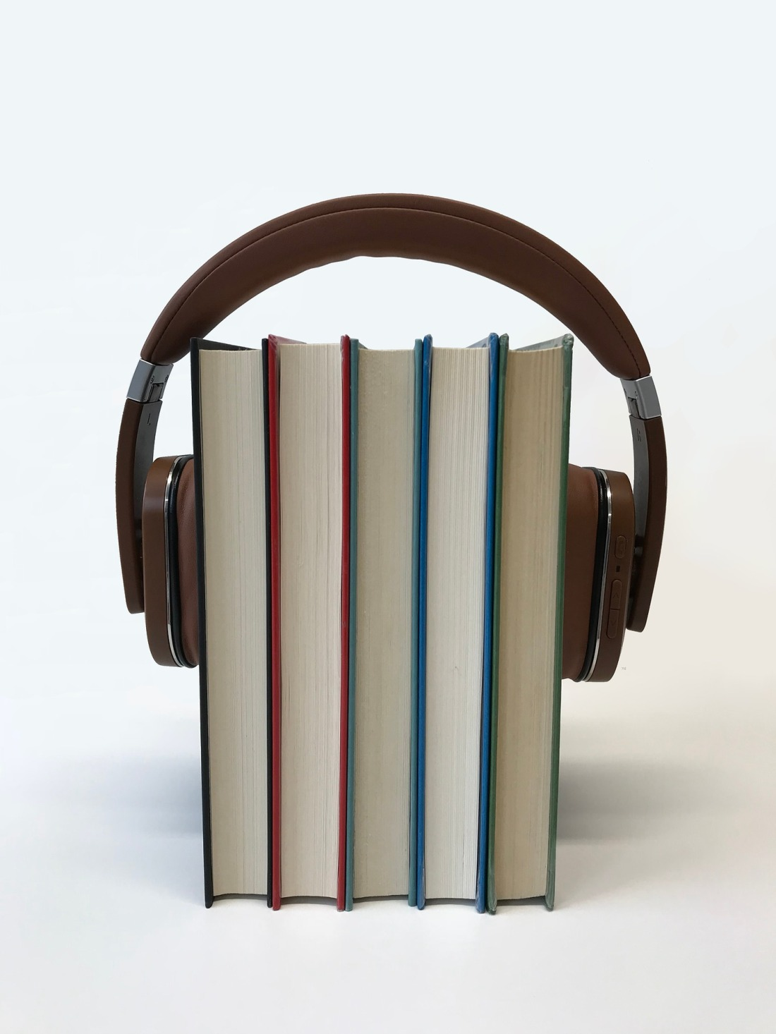 five books with a pair of headphones around them